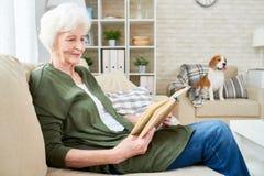 Усмехаясь старшая книга чтения женщины дома стоковая фотография rf