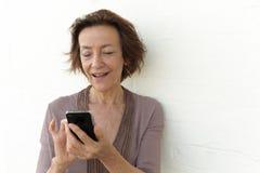 Усмехаясь старшая отправка СМС женщины Стоковые Изображения