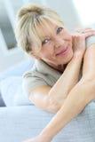 Усмехаясь старшая склонность женщины на софе Стоковая Фотография RF