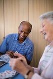 Усмехаясь старшего карточки человека и женщины играя Стоковая Фотография