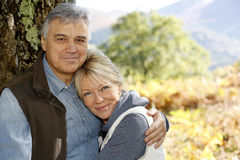 Усмехаясь старшие пары обнимая в лесе стоковая фотография rf