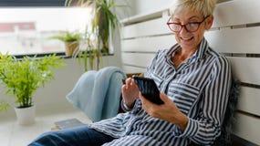 Усмехаясь старшие пары сидя в говорить парка стоковая фотография