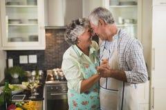 Усмехаясь старшие танцы пар в кухне стоковые изображения