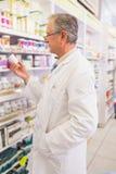 Усмехаясь старший аптекарь держа лекарство Стоковые Фотографии RF