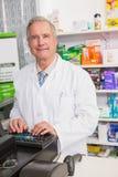 Усмехаясь старший аптекарь используя компьютер Стоковое Фото