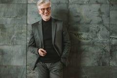 Усмехаясь старший бизнесмен стоя ослабленный Стоковые Изображения RF