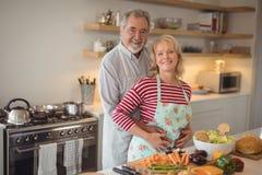 Усмехаясь старший один другого обнимать пар в кухне Стоковые Фотографии RF