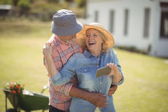 Усмехаясь старший один другого обнимать пар в саде Стоковая Фотография