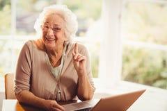 Усмехаясь старший палец повышения женщины используя компьтер-книжку Стоковое Изображение