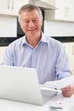 Усмехаясь старший человек проверяя домой финансы стоковое фото
