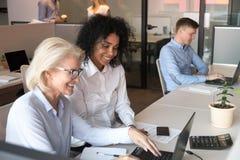 Усмехаясь старый ментор помогая африканскому интерну с ноутбуком в оф стоковое фото rf