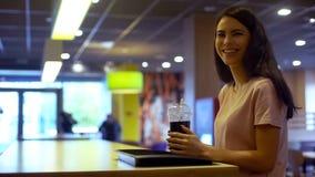 Усмехаясь стекло коктейля удерживания молодой женщины пластиковое, освежая carbonated вода стоковые фото