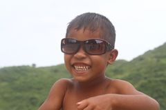 Усмехаясь стекла солнца азиатского мальчика нося стоковые фотографии rf