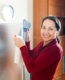Усмехаясь стекло зрелой женщины очищая Стоковые Изображения