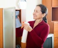 Усмехаясь стекло зрелой женщины очищая Стоковая Фотография