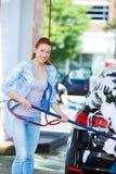 Усмехаясь стирка молодой женщины, чистка ее компактный автомобиль Стоковое Фото