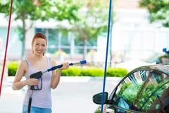 Усмехаясь стирка молодой женщины, чистка ее компактный автомобиль Стоковое Изображение