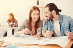 Усмехаясь студенты подготавливая их проект в архитектуре Стоковые Фото