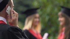 Усмехаясь студент-выпускник мужчины говоря на телефоне, defocused студентках общаясь сток-видео