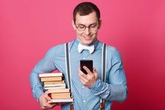 Усмехаясь студент со стогом книг, одетой рубашки в одном тоне, подтяжок и бабочки, сообщения recives с промежутком времени хороши стоковое изображение