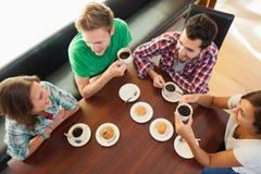 4 усмехаясь студента имея беседовать чашки кофе Стоковое Изображение RF