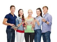 Усмехаясь студенты используя smartphones и ПК таблетки стоковая фотография