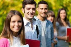 Усмехаясь студенты на парке стоковые фото