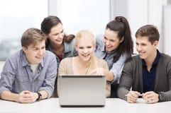 Усмехаясь студенты смотря компьтер-книжку на школе Стоковое фото RF
