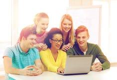 Усмехаясь студенты смотря компьтер-книжку на школе Стоковое Изображение