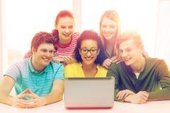 Усмехаясь студенты смотря компьтер-книжку на школе Стоковое Изображение RF