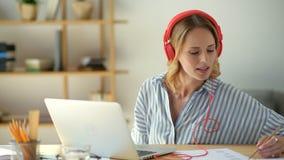 Усмехаясь студент в наушниках принимать онлайн курсы видеоматериал