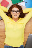 Усмехаясь студент в eyeglasses лежа на поле Стоковая Фотография RF