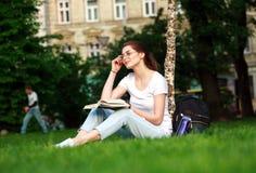 Усмехаясь студент девушки в городе паркует с книгой Стоковые Изображения RF