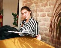 Усмехаясь студент девушки с книгой на образовании таблицы дома Стоковые Изображения RF
