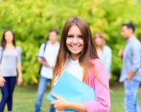 Усмехаясь студент держа книгу Стоковые Фото