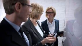 Усмехаясь счастливая бизнес-леди обсуждая с планами партнера, одобряет дело стоковые фото