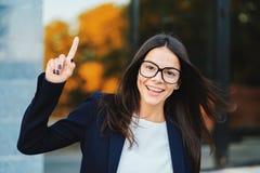 Усмехаясь счастливая девушка студента показывая жест eureka Портрет молодой думая обдумывая бизнес-леди имея идею стоковые фотографии rf