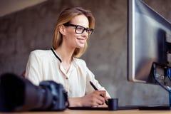 Усмехаясь счастливая женщина в стеклах сидя на таблице перед стоковые фото