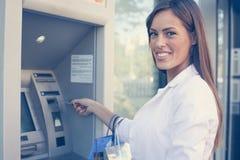 Усмехаясь счастливая женщина с хозяйственными сумками на ATM смотреть camer Стоковые Изображения