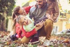 Усмехаясь счастливая семья играя совместно Стоковое Изображение