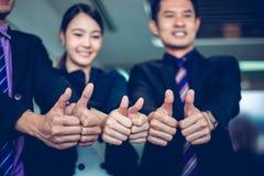 Усмехаясь счастливые бизнесмен и коммерсантки празднуя руку достижения успеха подняли и большой палец руки выставки вверх по конц стоковое фото rf