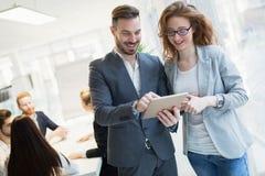 Усмехаясь счастливые коллеги работая на компании Стоковое Изображение