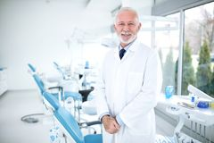 Усмехаясь, счастливый и удовлетворенный дантист на клинике стоковое изображение