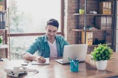 Усмехаясь счастливый студент работая с компьютером дома и preparin Стоковые Изображения