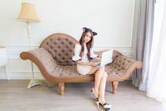 Усмехаясь счастливая женщина сидя на винтажной софе и использовании компьтер-книжки стоковое изображение