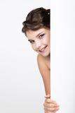 Усмехаясь счастливая молодая женщина стоя задней и полагаясь на белых пустых афише или плакате, выражает различную Стоковая Фотография