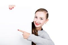 Усмехаясь счастливая молодая женщина стоя задней и полагаясь на белых пустых афише или плакате, выражает различную Стоковые Фотографии RF