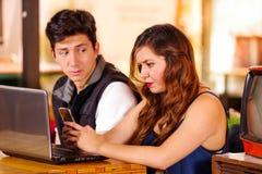 Усмехаясь счастливая пара на баре тратя время совместно, сумашедший человек смотрит и ее подруга пока она использует ее Стоковая Фотография RF