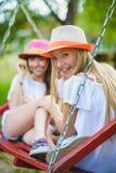 Усмехаясь счастливые подростковые кавказские девушки на качании Стоковые Изображения