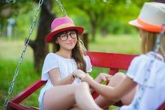 Усмехаясь счастливые подростковые кавказские девушки на качании Стоковое Изображение